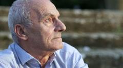 Profile of elderly man sunlit Stock Footage