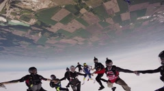Professional skydivers make big formation in sky. Extreme sport. Holding hands Stock Footage