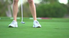 Close-up of a woman putting on the green while playing golf, slow motion. Stock Footage