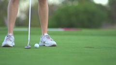 Close-up of a woman putting on the green while playing golf, super slow motion. Stock Footage
