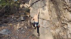 Shirtless young man rock climbing Stock Footage