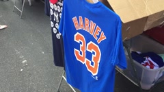 NEW YORK CITY: A Mets Matt Harvey shirt hangs next to a New York Yankees shirt Stock Footage