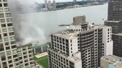 New York City firefighters respond to fire on top of section of building in Stock Footage