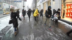 New York City: A city worker salts the sidewalks as commuters Stock Footage