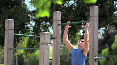 A man doing pull-ups at a park, slow motion. Stock Footage