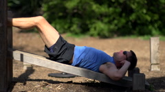 A man doing sit-ups at a park, slow motion. Stock Footage