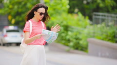 Happy young woman with map walking along city street in Europe asking help Stock Footage