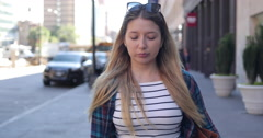 Young caucasian woman in city walking street sad serious face slow motion Stock Footage