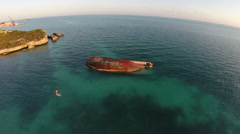 Aerial shot of young woman sup standup paddleboarding near a shipwreck in the Ca Stock Footage