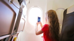 Adorable little girl traveling by an airplane sitting near window. Kid taking Stock Footage