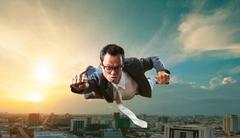 Business man flying over skyscraper for business successful and competition c Stock Photos