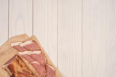 Smoked meat on a white wooden table. Stock Photos