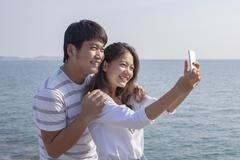Portrait of younger asian man and woman taking a photograph by smart phone ,r Stock Photos