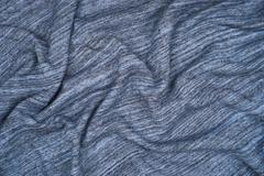 Creased knitted blue striped cloth material fragment as a background texture Kuvituskuvat