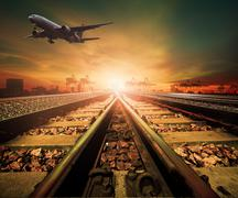 Track of railway and cargo plane flying above logistic ship port background f Stock Photos