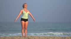 The back of a young woman doing yoga on the beach, slow motion. Stock Footage