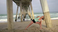 A young attractive woman doing yoga on the beach under a pier, slow motion. Stock Footage
