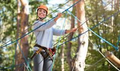 Young active woman doing a high ropes course Stock Photos
