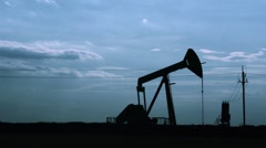 Silhouette of oil pumpjack at sunset. Motion of piston pumps, timelapse. Stock Footage