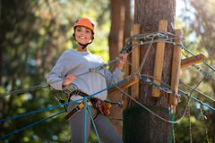 Young energetic woman spending her time in the adventure park Stock Photos
