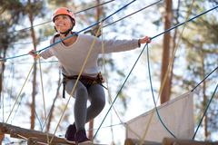 Happy enthusiastic woman having great time in the adventure park Stock Photos
