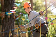 Good looking slim woman having a high wire adventure Stock Photos