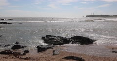 Waves crashing into sea rocks by the beach with Inubosaki Lighthouse in the Stock Footage
