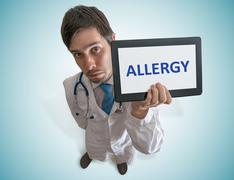 Doctor is showing tablet and warning against Allergy. View from top. Stock Photos