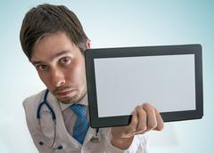 Doctor is showing blank and empty tablet for custom text. Stock Photos