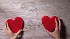 Young woman placing two red hearts on a wooden table, top view. Romance, love Stock Footage