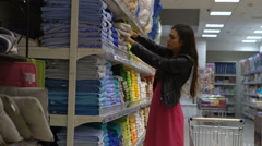 Young woman chooses towels in household goods section at the supermarket Stock Footage