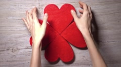 Girl taking four red hearts from a wooden table, top view. Care, love, Valentine Stock Footage
