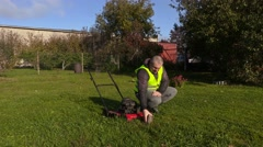 Worker pushing lawnmower and remove stone from lawn Stock Footage