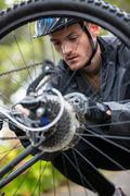 Male cyclist repairing his mountain bike Stock Photos