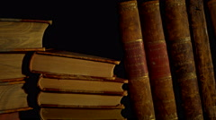 Old, aged books in a row on a wooden table. Stock Footage