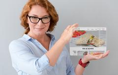 Delighted adult woman holding tablet Stock Photos
