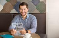 Cheerful man sitting at the table Stock Photos