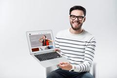 Amused young man smiling and holding laptop Stock Photos