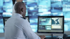 4K Surveillance officer communicating via earpiece in control room Stock Footage