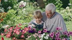 Elderly Man Teaching Granddaughter Gardening Stock Footage