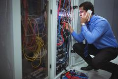 Technician talking on mobile phone while analyzing server Stock Photos
