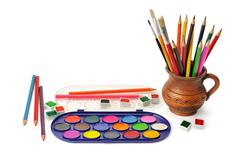 Watercolor paint and colored pencils Stock Photos