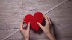 Girl ties up two red hearts with a lacy ribbon, top view. Romance, love Stock Footage