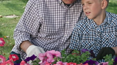 Grandfather Teaching Boy How to Remove Weeds Stock Footage