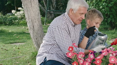 Grandfather and Grandson Watering Flowers Stock Footage