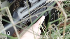 Detail Female soldier in meadow aims target Stock Footage