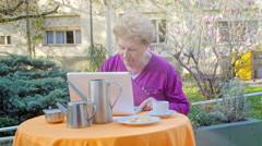 Old woman making breakfast using her laptop outdoor Stock Footage