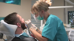 Dentist polishing patient's teeth. Steadicam. Arkistovideo