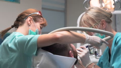 Dentist and assistant removing dental calculus from the teeth. Steadicam. Stock Footage