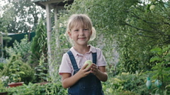Girl Eating Sour Apple in Green Garden Stock Footage